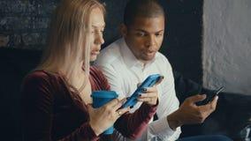 Par för blandat lopp genom att använda smartphonen i kafé eller kontorsbakgrund Man och kvinna att meddela och använda smartphone arkivfilmer