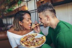 Par för blandat lopp som äter pizza i modernt kafé Arkivbild