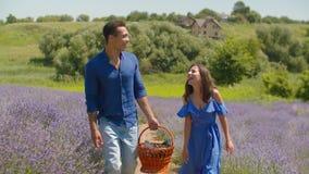 Par för blandat lopp som går med korgen i lavendelfält arkivfilmer