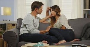 Par för blandat lopp som talar på soffan arkivfoton