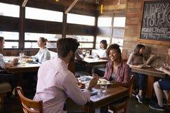 Par för blandat lopp som tycker om lunch i en upptagen restaurang Royaltyfri Fotografi