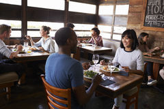 Par för blandat lopp som tycker om lunch i en upptagen restaurang Arkivfoto