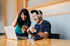 Par för lycklig förbindelse som firar seger i internetlotterit som håller ögonen på online-TV-sändning på smartphone- och bärbar  royaltyfri foto