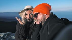 Par för Pov-skotthandelsresande i hatten som poserar att le överföra luftkyssen och dra framsidan som tar selfie lager videofilmer
