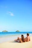 Par för strandsemestersolbränna som kopplar av i Hawaii Arkivfoton