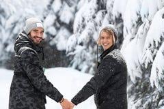 Par för ung man som går i snö Forest Outdoor Guys Holding Hands arkivfoto