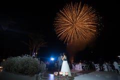 Par för fyrverkerier för destinationsstrandbröllop som ser Royaltyfri Foto