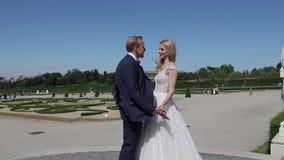 Par går nära den stora slotten Elegant brudgum och brud i deras gifta sig kläder Förälskelse arkivfilmer