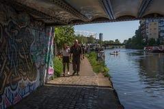 Par går under en bro på floden Lea London royaltyfri fotografi