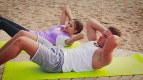 Par gör övningar på stranden stock video