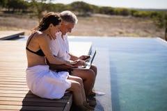 Par genom att använda bärbara datorn nära poolside Arkivbilder