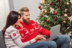 Par genom att använda bärbara datorn på christmastime arkivfoto