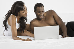 Par genom att använda bärbara datorn på säng royaltyfria foton