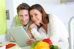 Par genom att använda den digitala minnestavlan i kök Royaltyfri Fotografi