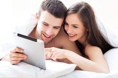 Par genom att använda den digitala minnestavlan i säng Royaltyfri Fotografi