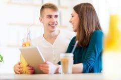 Par genom att använda den digitala minnestavlan på kafét Fotografering för Bildbyråer