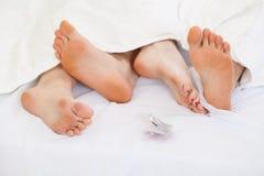 Par genom att använda det att använda preventivmedel i säng Fotografering för Bildbyråer