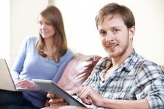 Par genom att använda Digital teknologi hemma Royaltyfri Foto