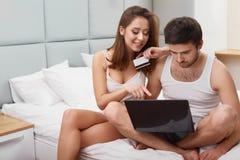 Par genom att använda kreditkorten för att shoppa på internet Arkivfoton