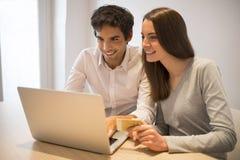 Par genom att använda kreditkorten för att shoppa på linje Bärbar dator Inomhus skrivbord Arkivbilder