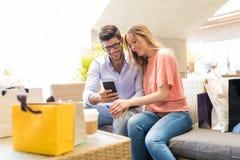Par genom att använda mobiltelefonen i kafé på gallerian royaltyfri fotografi