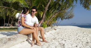 Par genom att använda talande sammanträde för cellSmart telefon på stranden under palmträd, lycklig le man och kvinna stock video