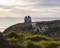 Par håller ögonen på solnedgången efter cykelritt royaltyfri bild