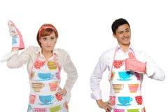 Par-homem de cozimento engraçado na mulher do avental e do cozinheiro chefe Imagem de Stock