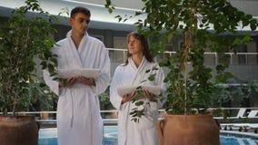 Par i badrockar som rymmer handdukar stock video