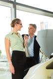 Par i bilåterförsäljare som ser under en huv Royaltyfri Fotografi