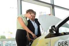 Par i bilåterförsäljare som ser under en huv Arkivbild