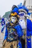 Par i blått- och gulingdräkter poserar på den Venedig karnevalet Fotografering för Bildbyråer