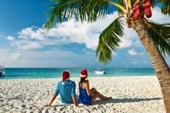 Par i blåttkläder på en strand på jul Arkivfoton