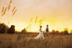 Par i bröllop klär mot bakgrunden av fältet på solnedgången, bruden och brudgummen Arkivfoton