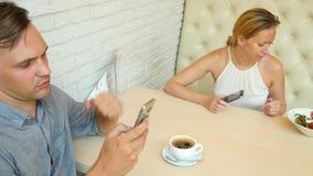 Par i Cafe Man och härlig kvinna på ett datum Alla ser hans mobiltelefon 4K långsam rörelse stock video