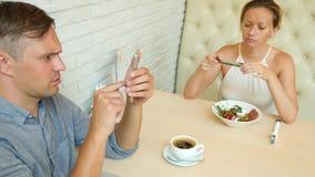 Par i Cafe Man och härlig kvinna på ett datum Alla ser hans mobiltelefon 4K långsam rörelse arkivfilmer