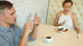 Par i Cafe Man och härlig kvinna på ett datum Alla ser hans mobiltelefon 4K långsam rörelse lager videofilmer