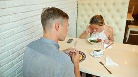 Par i Cafe Man och kvinna på ett datum 4K långsam rörelse arkivfilmer