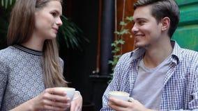Par i Cafe Ungdomarsom dricker kaffe och meddelar lager videofilmer