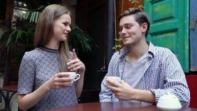 Par i Cafe Ungdomarsom dricker kaffe och meddelar stock video