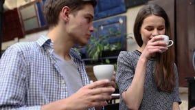 Par i Cafe Ungdomarsom dricker kaffe och meddelar arkivfilmer