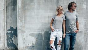 Par i grå t-skjorta över gataväggen Arkivfoton