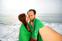 Par i handdukar på stranden arkivbilder
