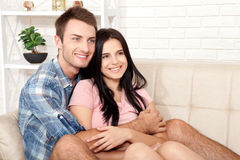 Par i hans nya hem Härliga par som kramar och ser kameran som ler sammanträde på soffan i vardagsrum Arkivbild