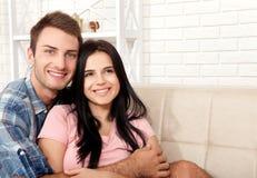 Par i hans nya hem Härliga par som kramar och ser kameran som ler sammanträde på soffan i vardagsrum Fotografering för Bildbyråer
