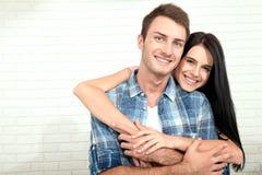 Par i hans nya hem Härliga par som kramar och ser kameran som ler sammanträde på soffan i vardagsrum Royaltyfri Bild