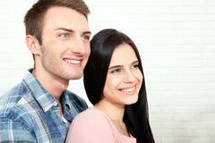 Par i hans nya hem Härliga par som kramar och ser kameran som ler sammanträde på soffan i vardagsrum Arkivfoton