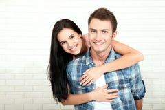 Par i hans nya hem Härliga par som kramar och ser kameran som ler sammanträde på soffan i vardagsrum Royaltyfri Fotografi