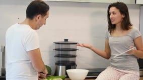 Par i hem- kök Mannen förbereder sallad och kvinnan som använder den elektroniska minnestavlan stock video