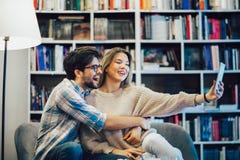 Par i inomhus kaf? genom att anv?nda den digitala minnestavlan och ha gyckel royaltyfria foton